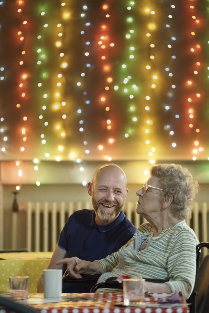 Man smiles at woman with coloured lights behind